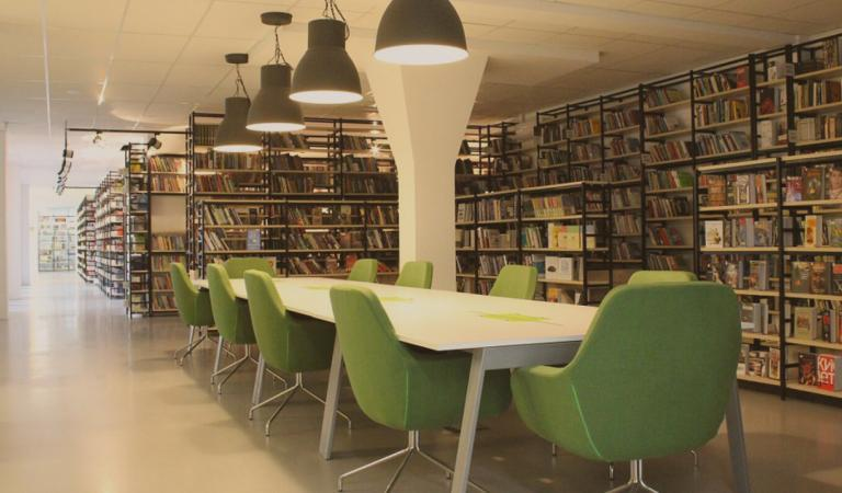 Library with desk and green chairs